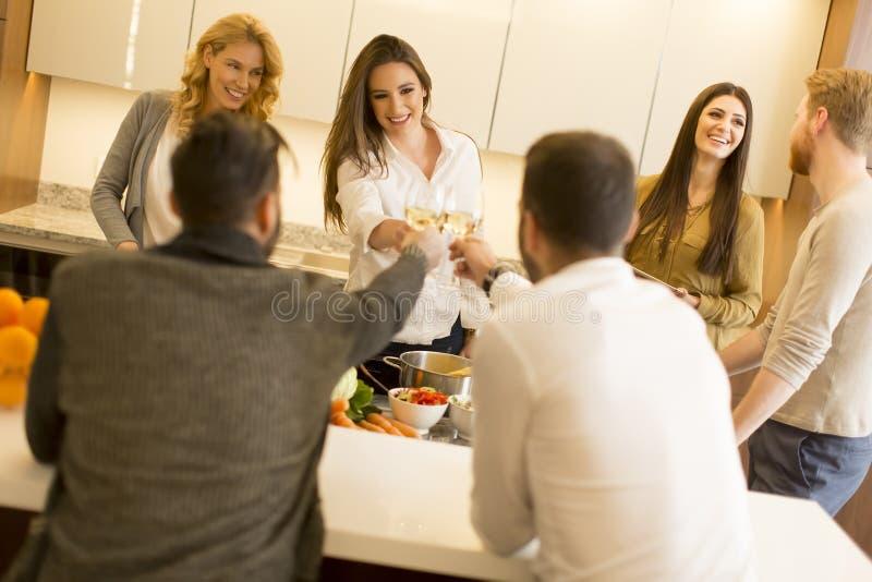 Groep jongeren die diner hebben en wijn in modern drinken stock foto's
