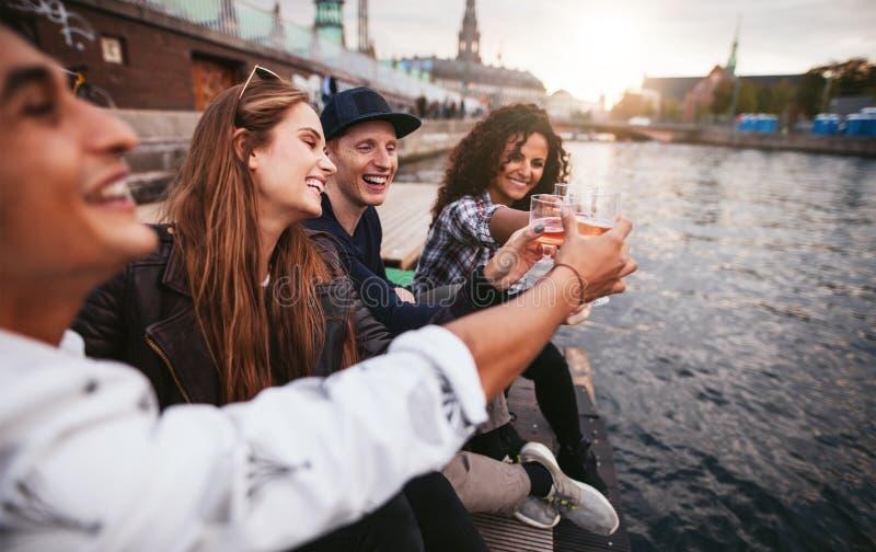 Groep jongeren die dranken hebben bij meer stock afbeelding