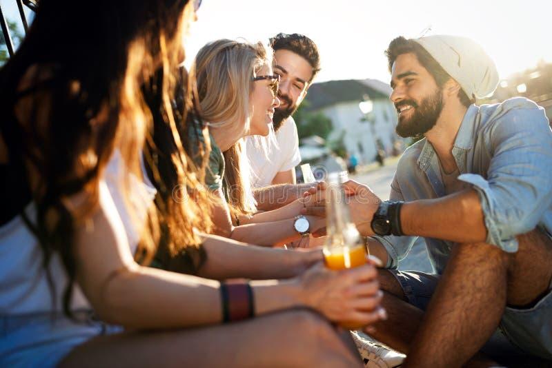 Groep jongeren die, en pret samen glimlachen spreken hebben stock afbeelding