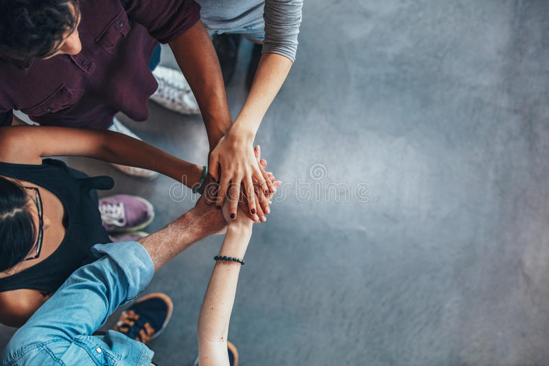 Groep jongeren die hun handen stapelen stock foto