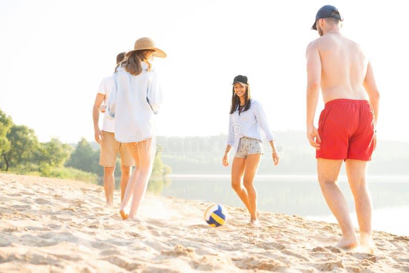 Groep jongeren die met bal bij het strand spelen Jonge vrienden die de zomer van vakantie op een zandig strand genieten royalty-vrije stock afbeeldingen