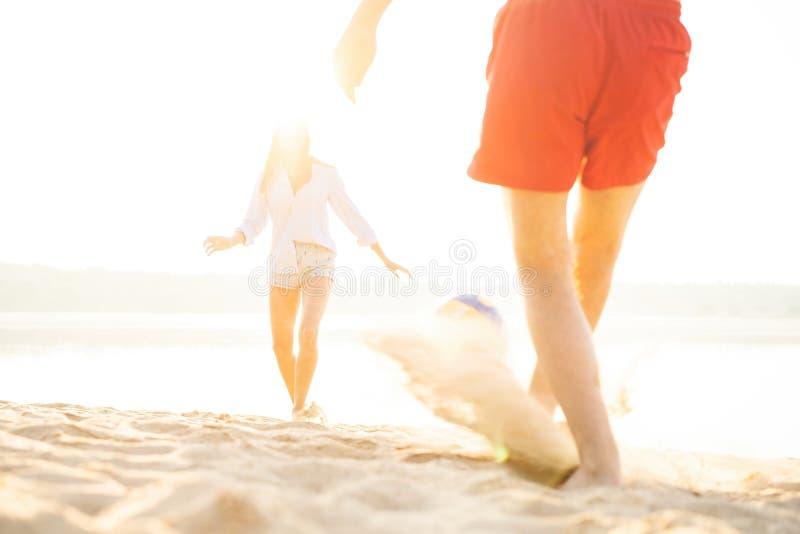 Groep jongeren die met bal bij het strand spelen Jonge vrienden die de zomer van vakantie op een zandig strand genieten stock foto