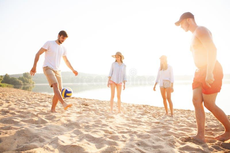 Groep jongeren die met bal bij het strand spelen Jonge vrienden die de zomer van vakantie op een zandig strand genieten royalty-vrije stock foto