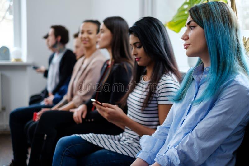 Groep jongeren die op een afgietsel of baangesprek wachten royalty-vrije stock afbeelding