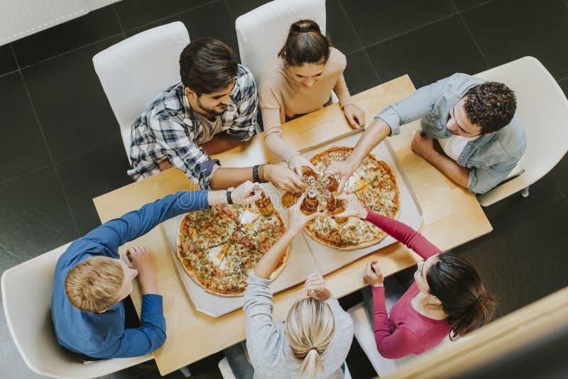 Groep jongeren die pizza eten en cider drinken stock afbeeldingen