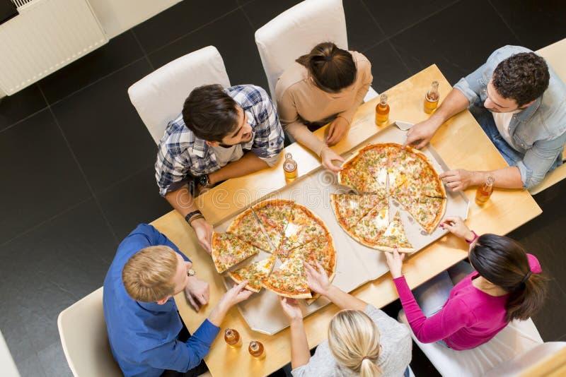 Groep jongeren die pizza eten en cider drinken stock foto