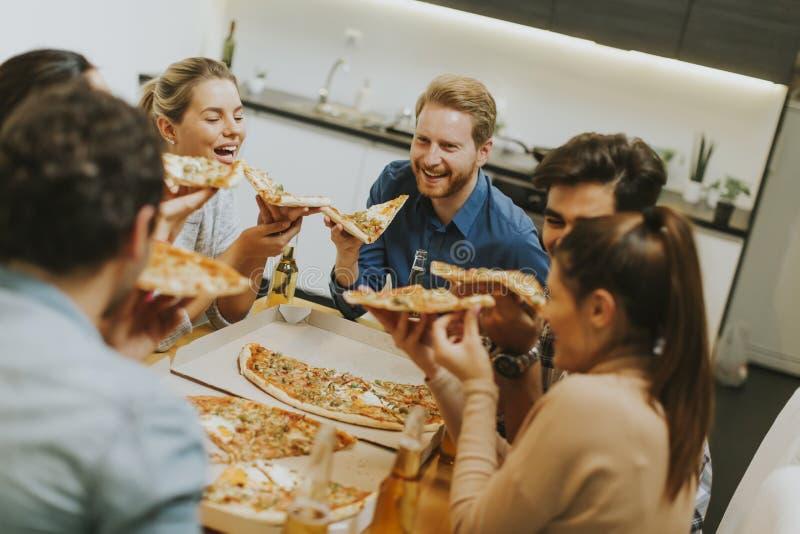 Groep jongeren die pizza eten en cider drinken royalty-vrije stock foto's