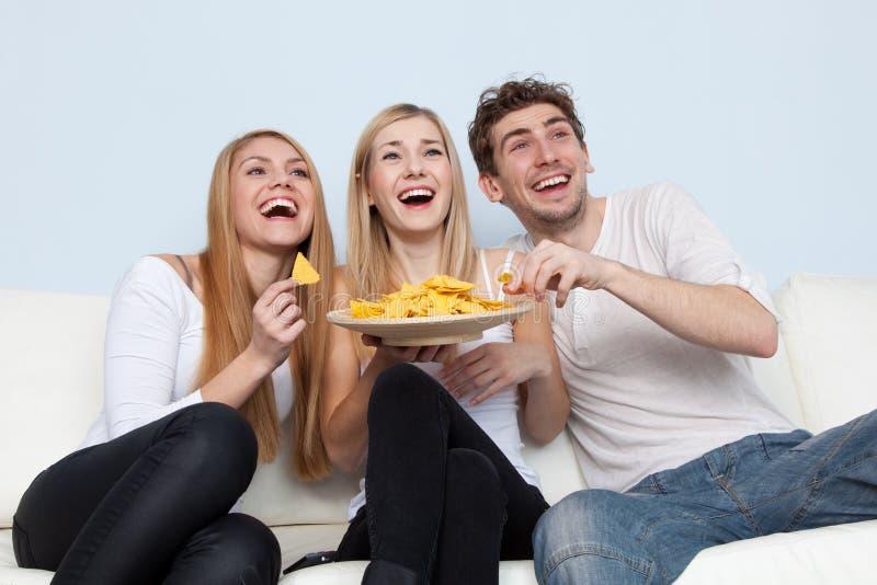 Groep jongeren die pizza thuis eten royalty-vrije stock afbeelding