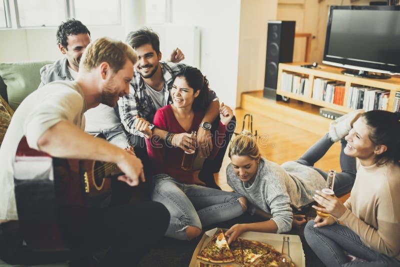 Groep jongeren die pizzapartij hebben stock afbeelding