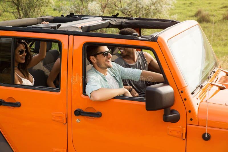 Groep jongeren die pret hebben samen door een auto te drijven royalty-vrije stock afbeeldingen