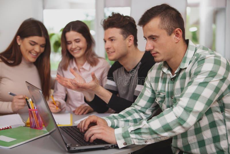 Groep jongeren die samen bij universiteitsklaslokaal bestuderen stock foto