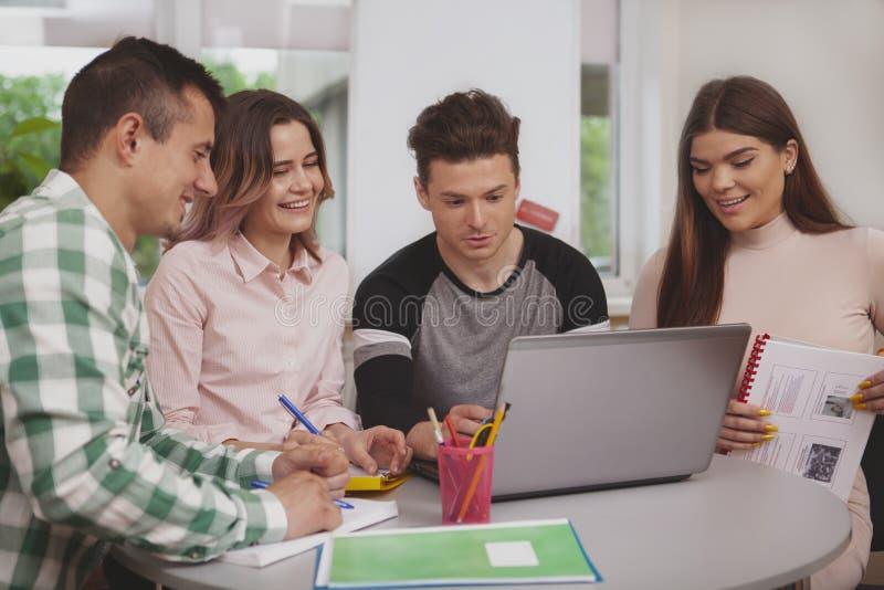 Groep jongeren die samen bij universiteitsklaslokaal bestuderen stock afbeeldingen