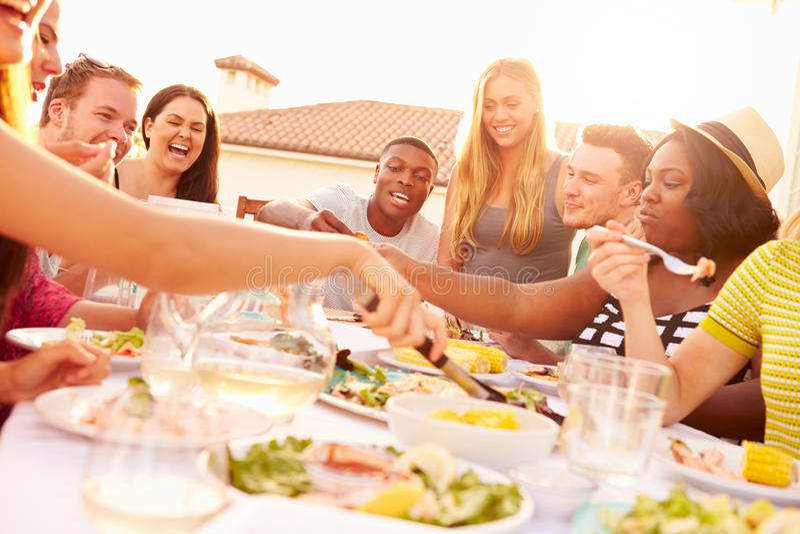 Groep Jongeren die van Openlucht de Zomermaaltijd genieten stock afbeelding
