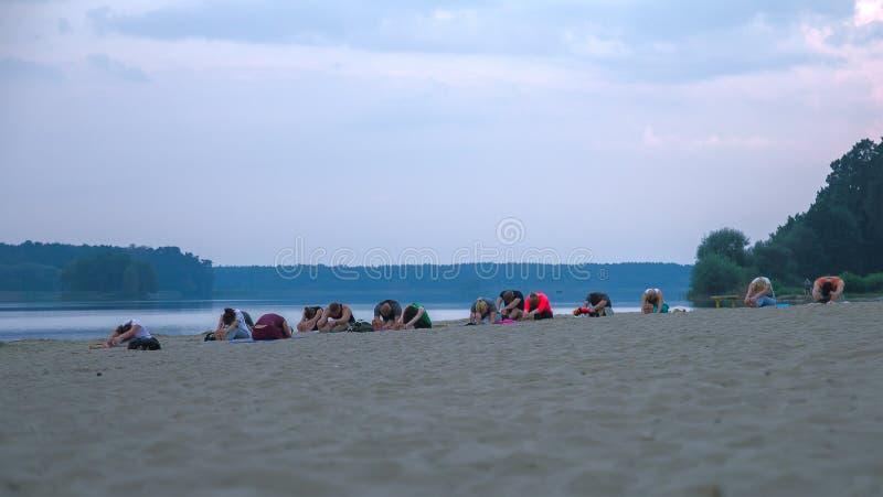 groep jongeren die yoga uitoefenen tijdens de zonsopgang royalty-vrije stock foto