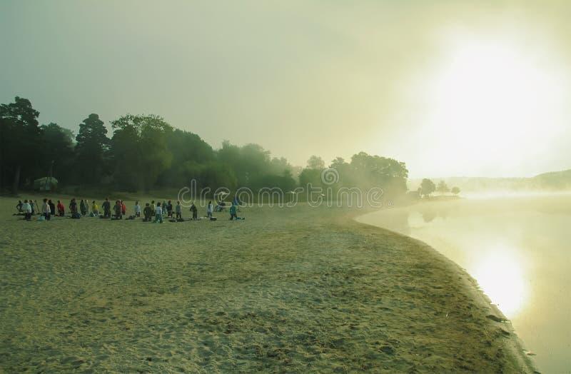 groep jongeren die yoga uitoefenen tijdens de zonsopgang royalty-vrije stock afbeeldingen