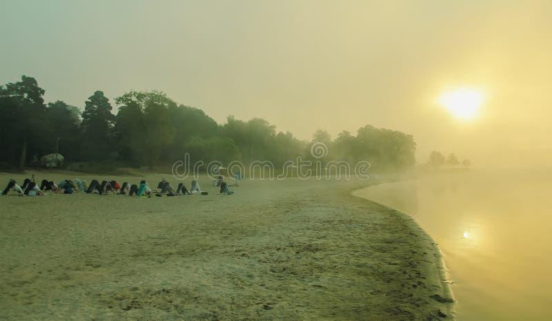groep jongeren die yoga uitoefenen tijdens de zonsopgang royalty-vrije stock foto's