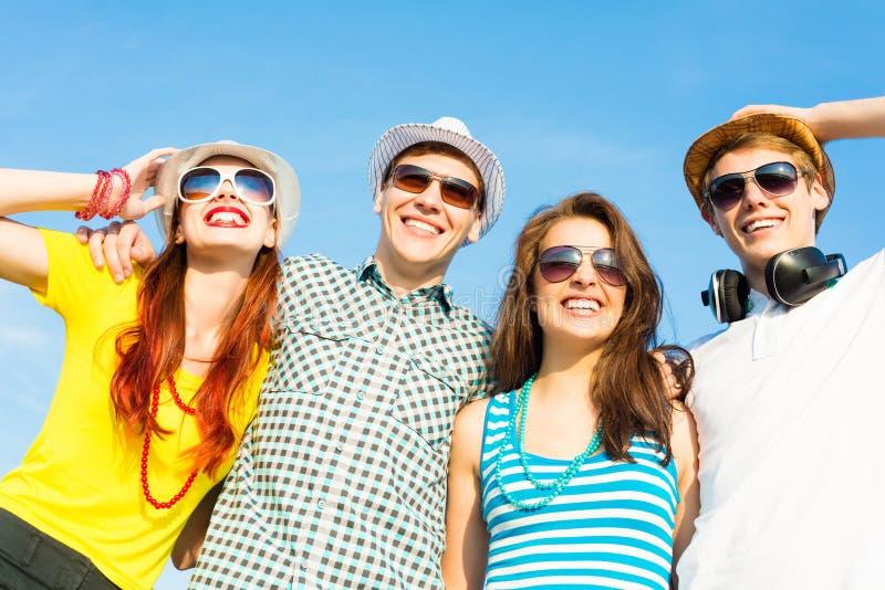 Groep jongeren die zonnebril en hoed dragen stock afbeeldingen