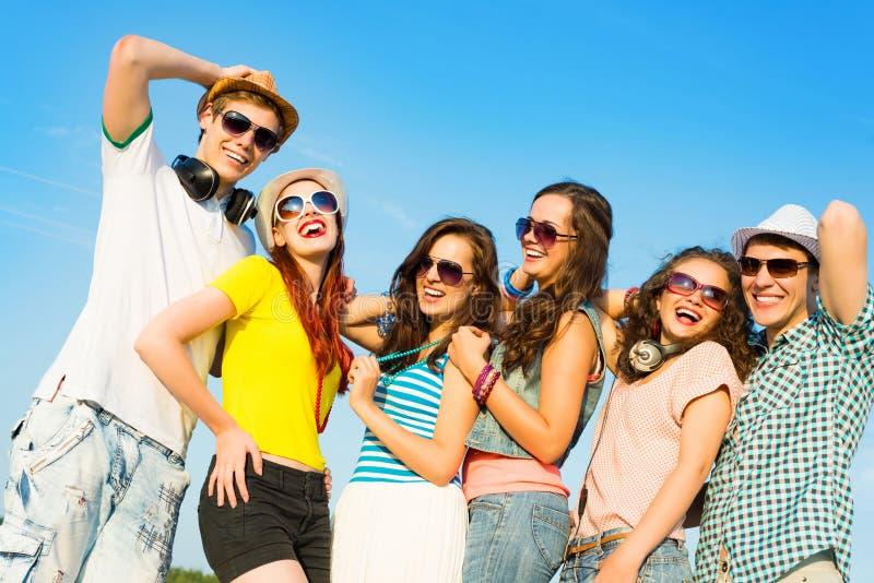 Groep jongeren die zonnebril en hoed dragen stock afbeelding