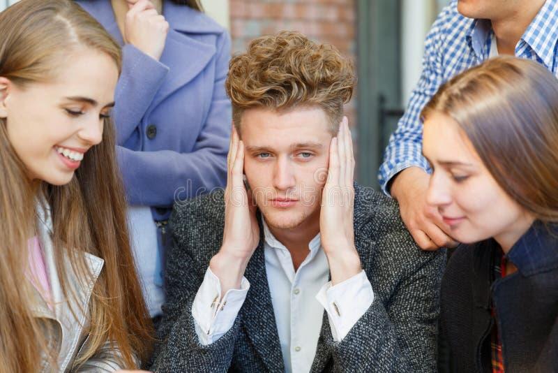 Groep jongeren in een koffie De kerel houdt zijn hoofd royalty-vrije stock fotografie