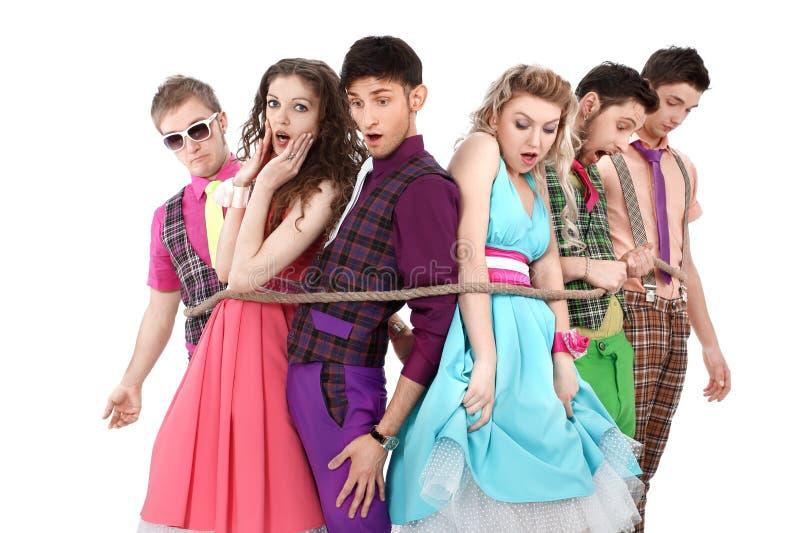 Groep jongeren in heldere die kleren, met een kabel wordt gebonden stock afbeeldingen