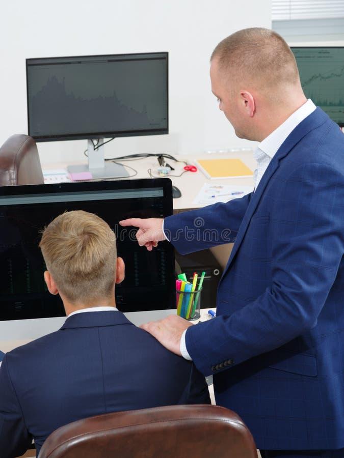 Groep jongeren in het bureau die het computerscherm bekijken royalty-vrije stock foto's