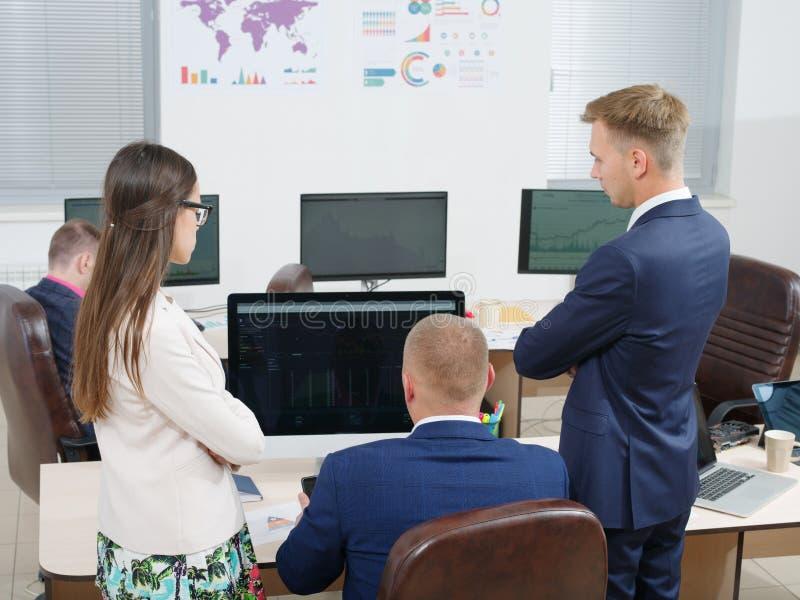 Groep jongeren in het bureau die het computerscherm bekijken royalty-vrije stock foto