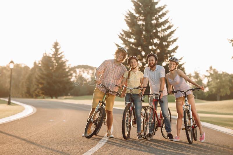 Groep jongeren met fietsen op de weg stock foto's
