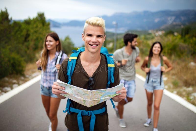 Groep jongeren met rugzakken die samen door de weg lopen stock fotografie