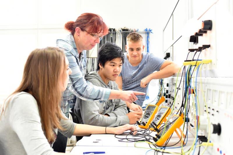 Groep jongeren in technische beroepsopleiding met teac stock foto