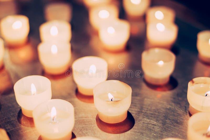 Groep kaarsen in kerk Kaarsen lichte achtergrond stock fotografie