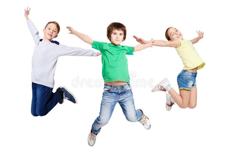 Groep kinderen die bij wit geïsoleerde studioachtergrond springen stock afbeeldingen