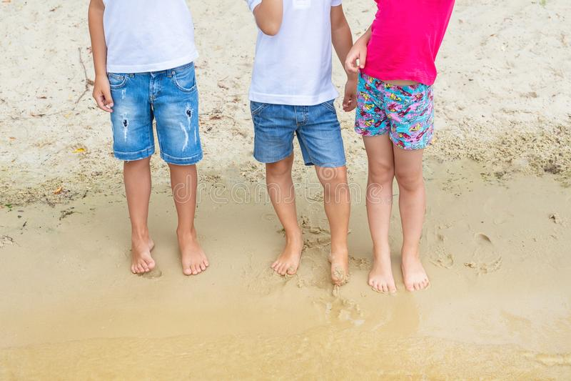 Groep kinderen die casaual denimborrels dragen die pret hebben die zich op zand bij strand bevinden Drie peutervrienden die spele stock foto
