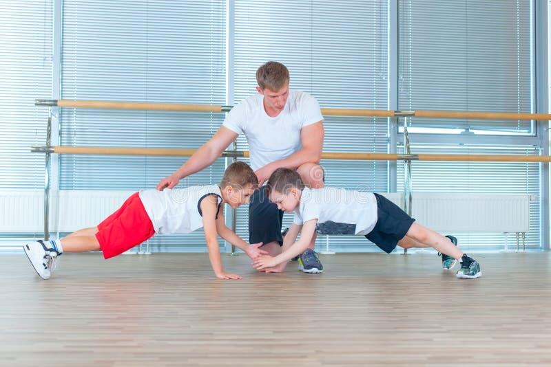 Groep kinderen die jonge geitjesgymnastiek in gymnastiek met leraar doen Gelukkige sportieve kinderen in gymnastiek baroefening p stock afbeeldingen