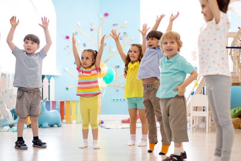 Groep kinderen die jonge geitjesgymnastiek in kleuterschool doen stock fotografie
