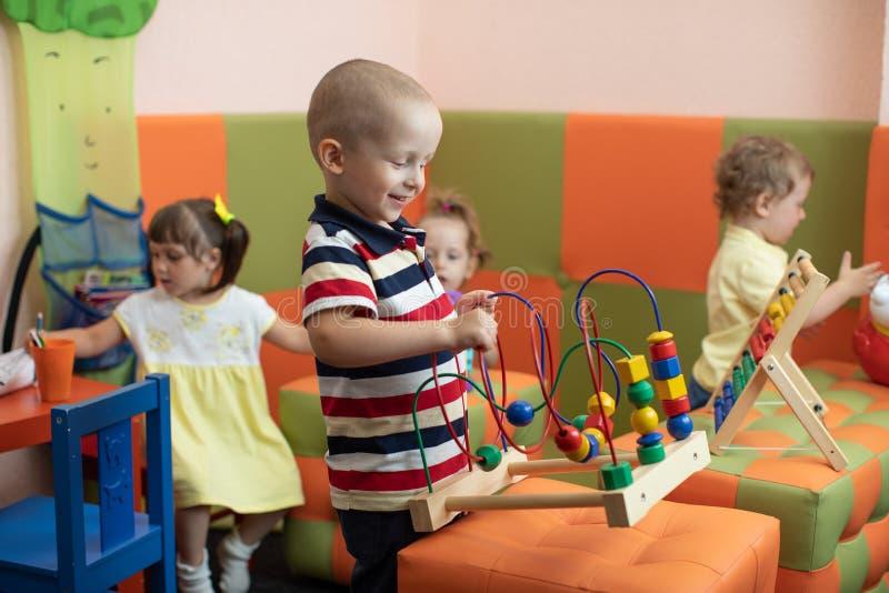 Groep kinderen die in kleuterschool of opvangcentrum spelen stock foto's