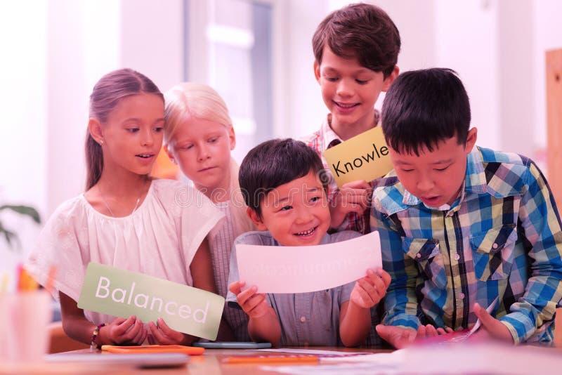 Groep kinderen die nieuwe Engelse woorden leren stock foto's