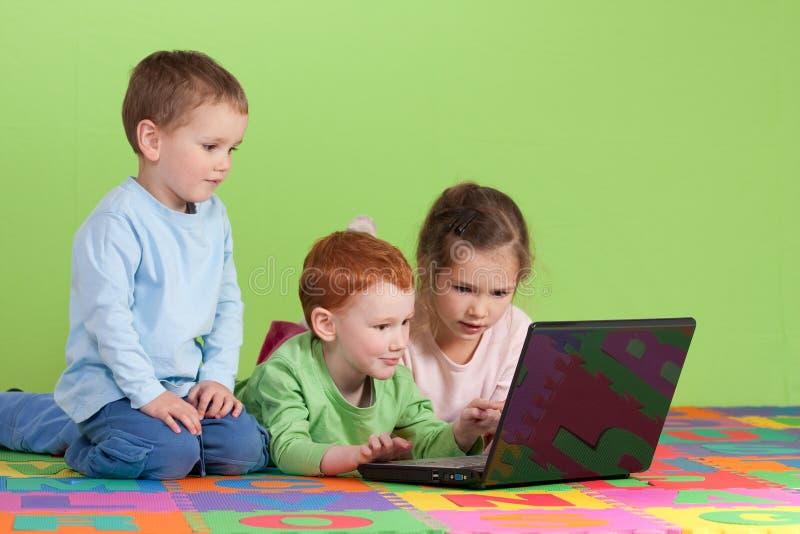 Groep kinderen die op jonge geitjescomputer leren stock foto's