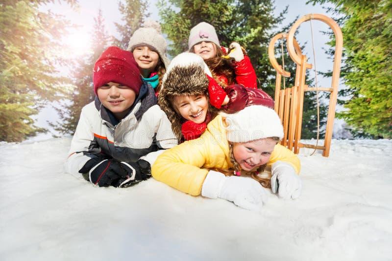 Groep kinderen die op sneeuw in de wintertijd spelen royalty-vrije stock foto