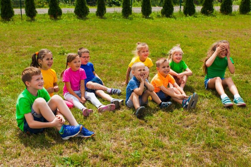 Groep kinderen die samen op het gras zitten royalty-vrije stock foto