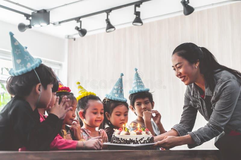 Groep kinderen die verjaardagscake in verjaardagspartij blazen die gelukkige verjaardag zingen stock foto's
