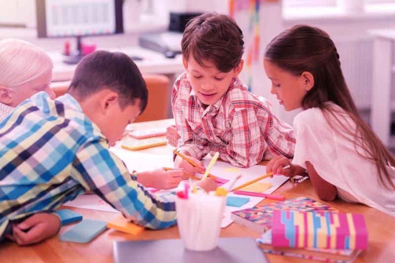 Groep kinderen die zich in het klaslokaal samentrekken royalty-vrije stock foto