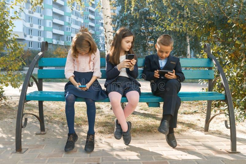 Groep kinderen 7, 8 jaar oud met mobiele telefoons die, enthousiast smartphones, schoolkinderen met rugzakken, uit onderzoeken stock afbeeldingen