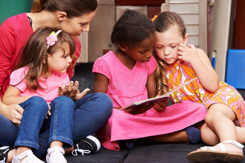 Groep kinderen met boek in kleuterschool royalty-vrije stock fotografie