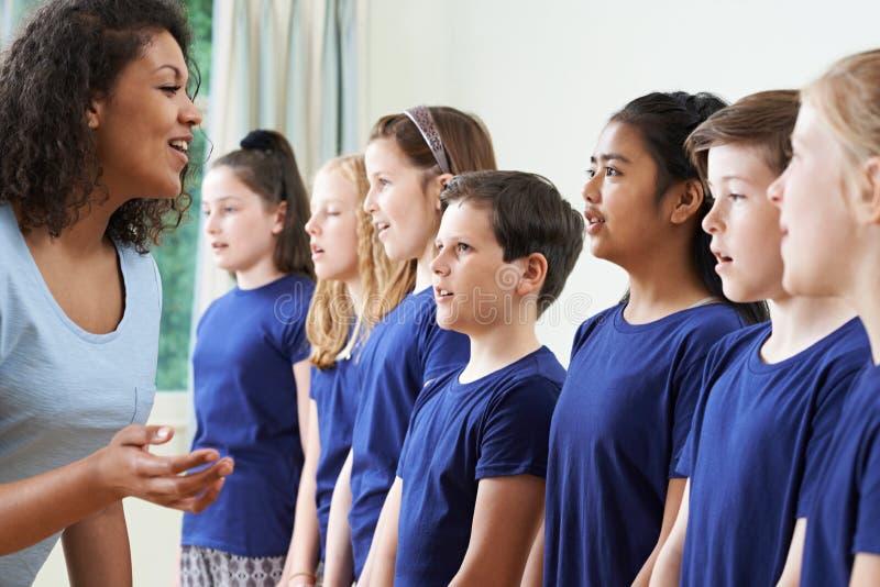 Groep Kinderen met Leraar Enjoying Singing Group stock foto's