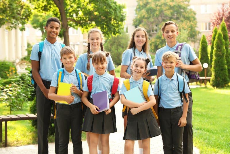 Groep kinderen in modieuze eenvormige school stock foto's