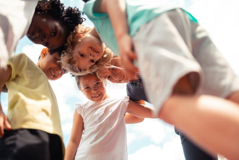 Groep kinderen spreken die vooruit aan elkaar leunen stock afbeelding