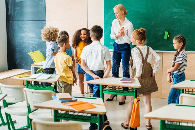 groep klasgenoten die zich rond leraar bevinden royalty-vrije stock afbeelding