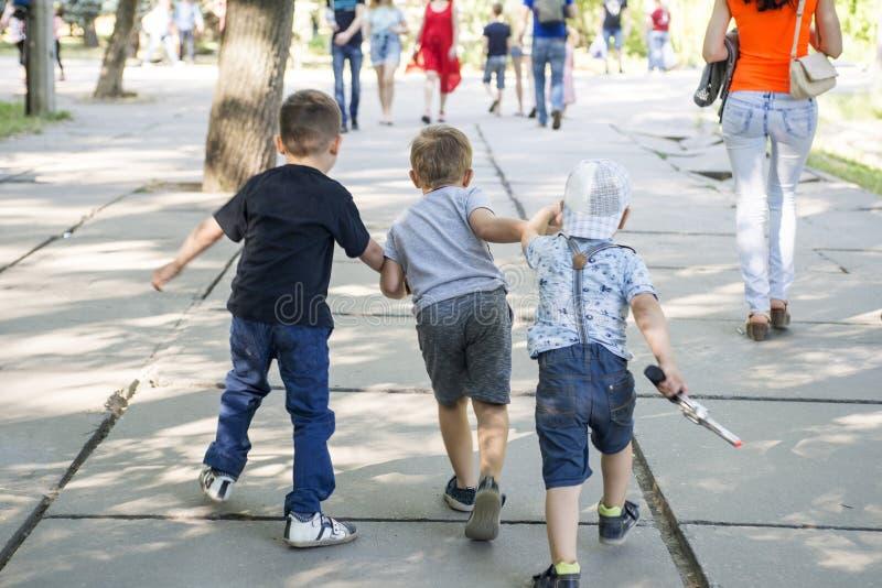 Groep kleine kinderen die in park lopen Gelukkige groep die jonge geitjes bij het park spelen stock foto's