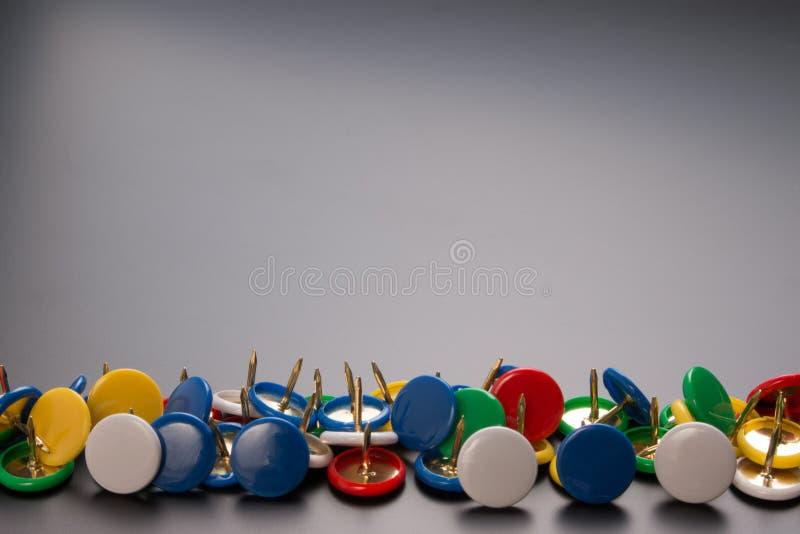 Groep kleurrijke duwspelden op zwarte raad stock foto