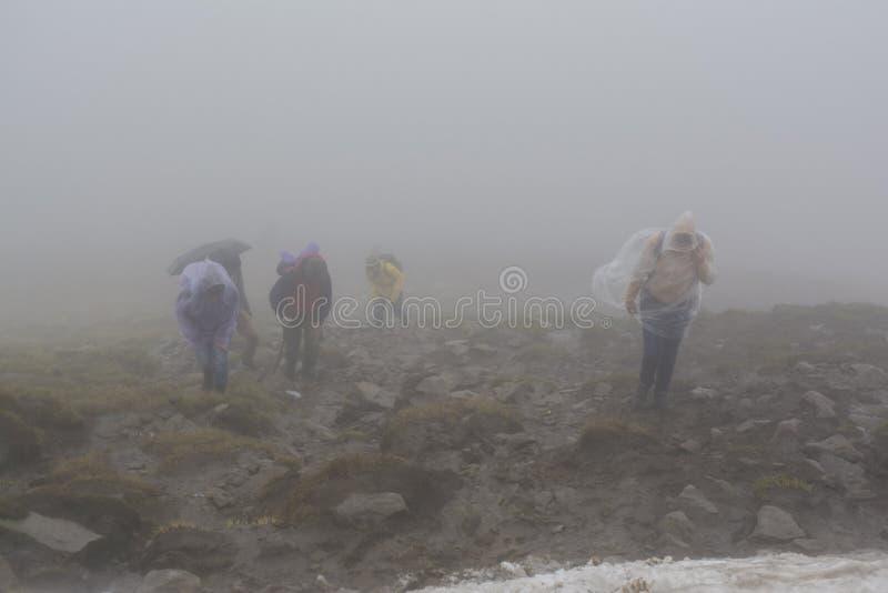 Groep klimmers in regenjassen tijdens regenachtige en winderige dag royalty-vrije stock fotografie